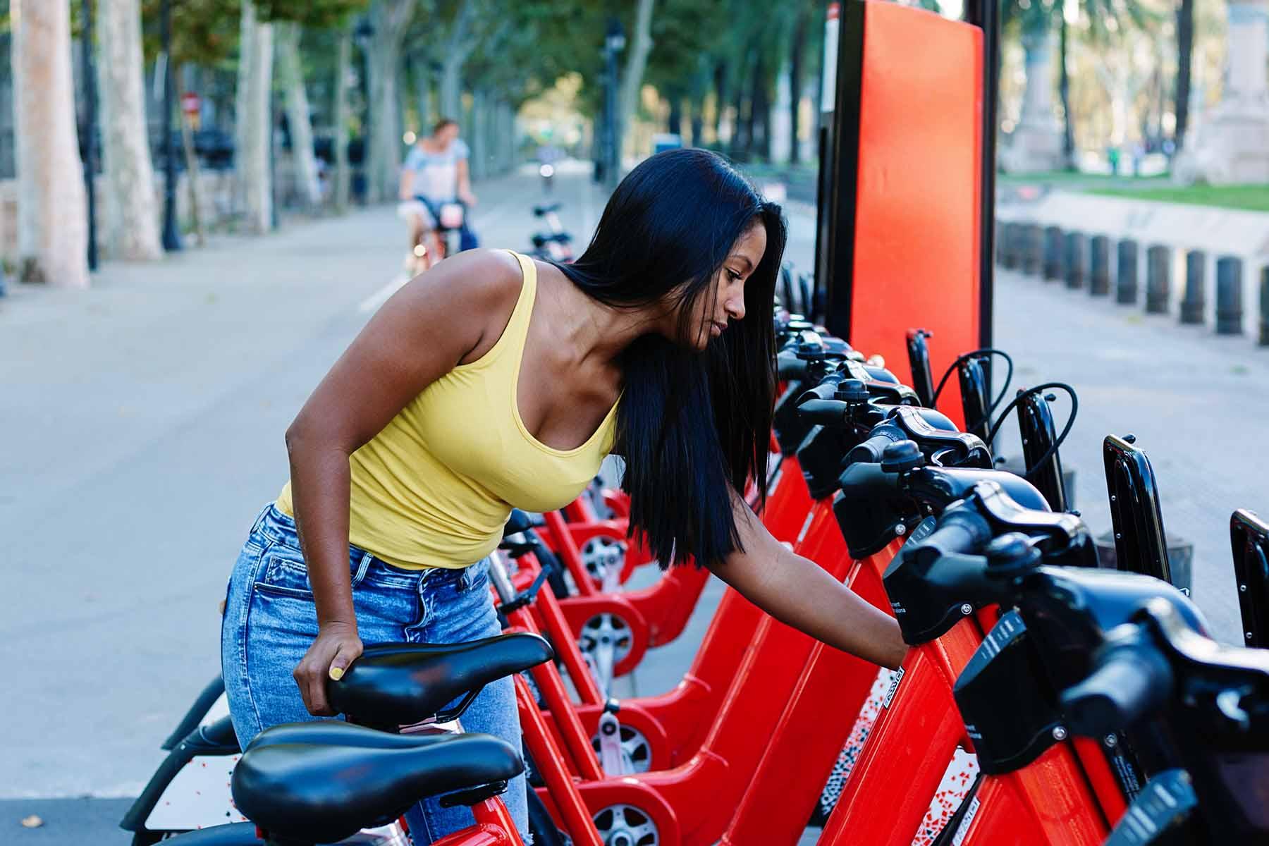 Young woman taking a rental bike